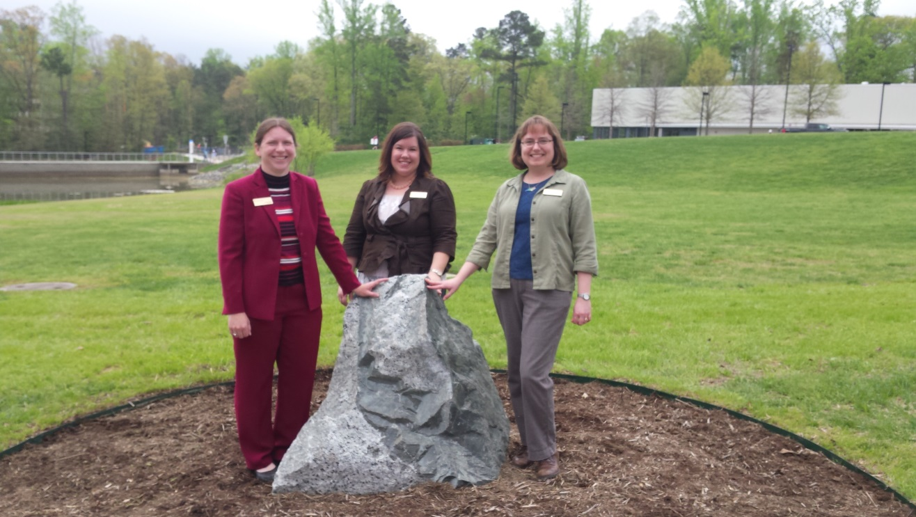Figure 11: Geologists Dr. Sara Rutzky, Stephanie Rollins, and Gretchen Miller pose with one of the boulders at Northern Wake Campus after the April 14, 2015 dedication ceremony.