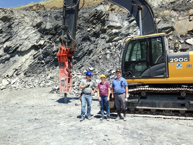 Figure 4: Geologists Tyler Clark, Dr. Sara Rutzky, and Dr. Ken Howard pose in front of a hydraulic hammer during a visit to a quarry to select boulders for the Outdoor Geology Lab in May 2014.