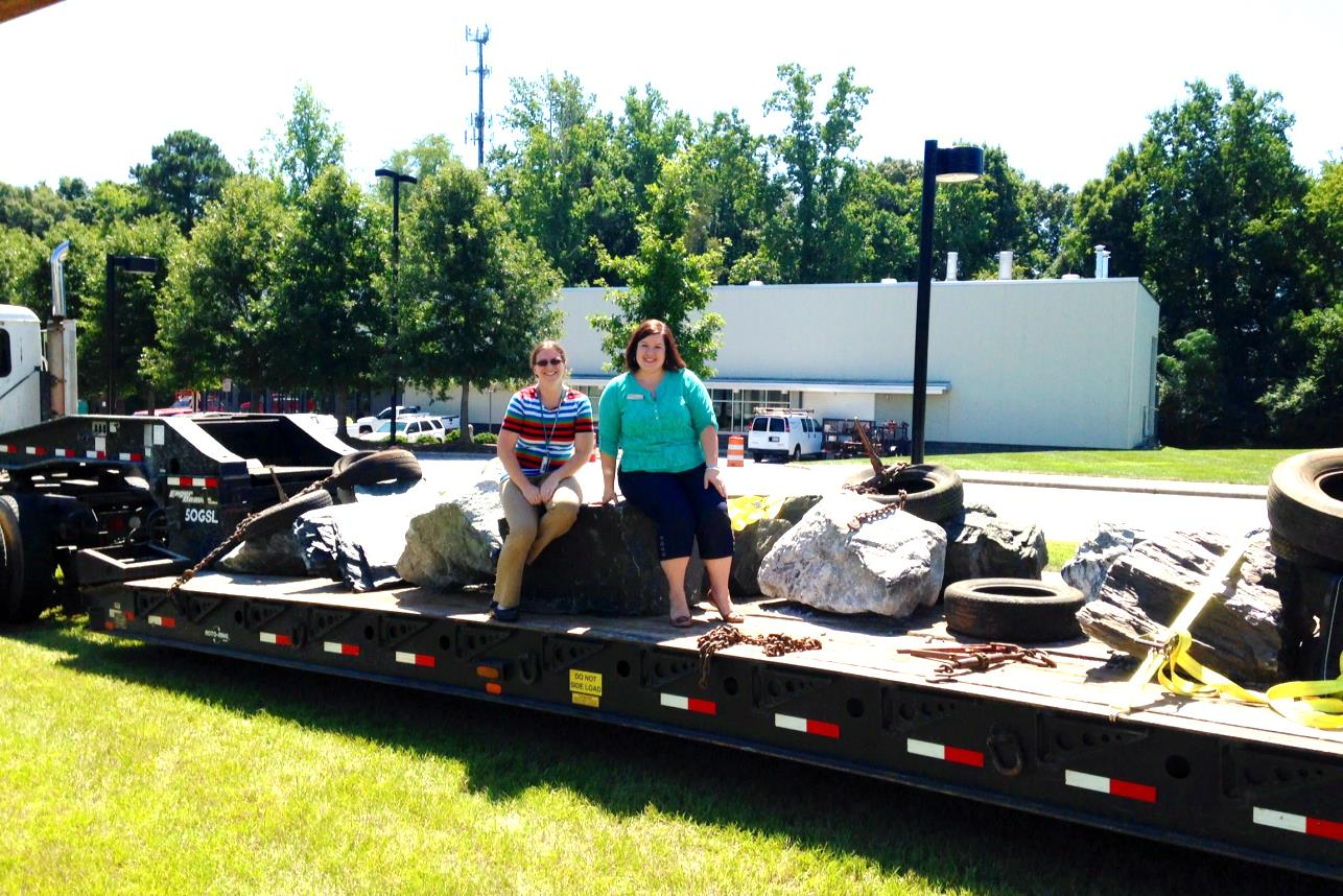 Figure 7: Geologists Dr. Sara Rutzky and Stephanie Rollins pose with the boulders as they are delivered to Wake Tech's Northern Wake Campus on August 27,  2014.