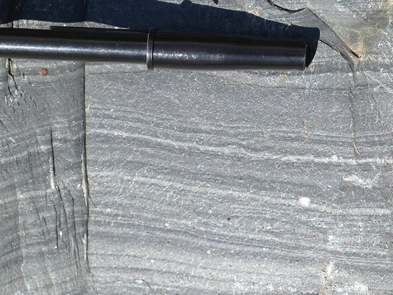 Figure 6: Another image showing the bedding planes; black ballpoint pen for scale. The straight lines and thinness of these layers suggest calm, quiet waters where sediment could slowly accumulate.